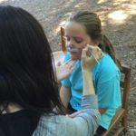 girl having face painted like a cat